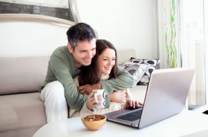 Beautiful young couple relaxing in a living room and using laptop